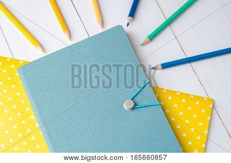Blue notebook with color pencils on yellow paper and white wooden background
