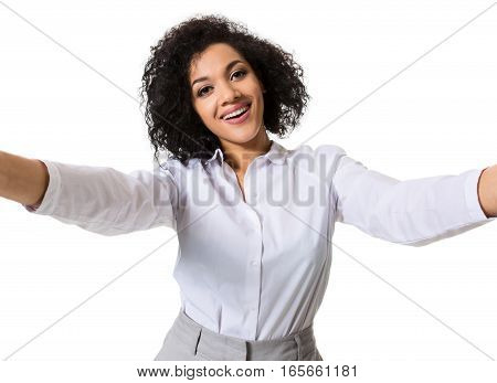 Young beautiful African American woman makes self against the white background in studio. Emotions. Isolated on white background