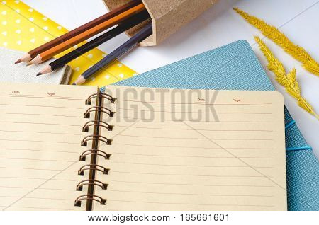 Blank daily planner notebook with color pencils on white wooden background