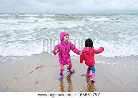 Two Little Sisters Having Fun On A Sandy Beach Of Baltic Sea