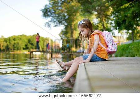 Two Cute Little Girls Sitting On A Wooden Platform By The River Or Lake