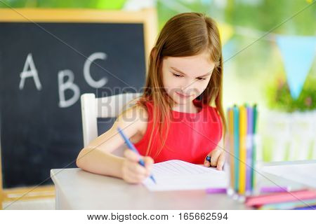 Cute Little Girl Drawing With Colorful Pencils At A Daycare