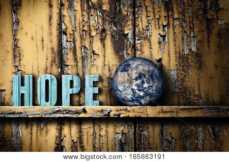 Earth on the shelf on worn wooden background. Concept of hope for the health of the planet or humanity in general. Contrast between the grunge background and significance of elements lying on the shelf.