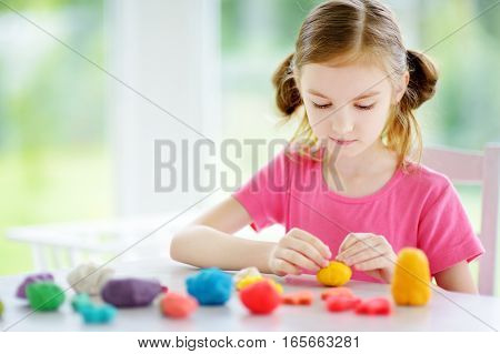 Cute Little Girl Having Fun With Colorful Modeling Clay At A Daycare