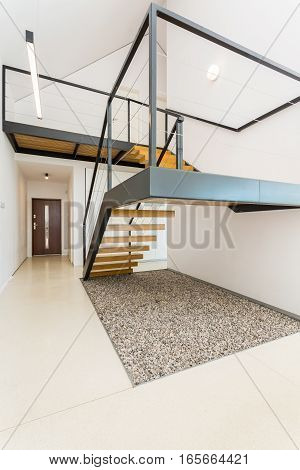 White and spacious interior with mezzanine stairs mezzanine entrance door in the background