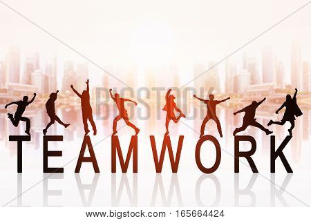 Group of silhouette peoples jumping over the words : TEAMWORK with blurred cityscape background concept for business team work.