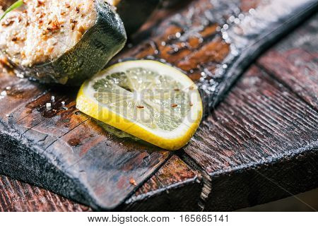 Wooden serving board with salmon steak and lemon slice. Closeup view. Selective focus