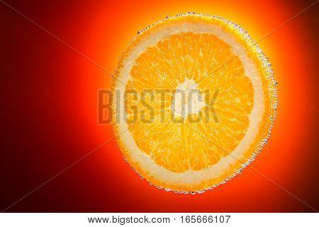 Fresh orange slice in water with bubbles on orange gradient background