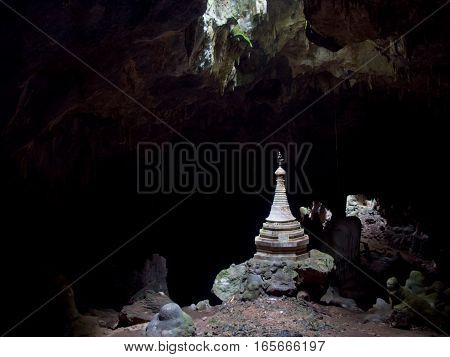 A lone Buddhist stupa is illuminated by a natural skylight in a dark cave in Myanmar