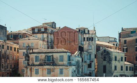 Cascade of peeling old mediterranean houses against clear blue sky - Corfu Greece