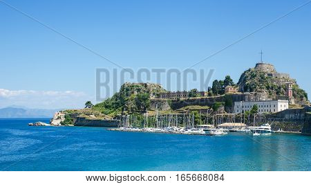 Scenery view of blue sea and boats moored near ancient mediterranean castle on Corfu island Greece