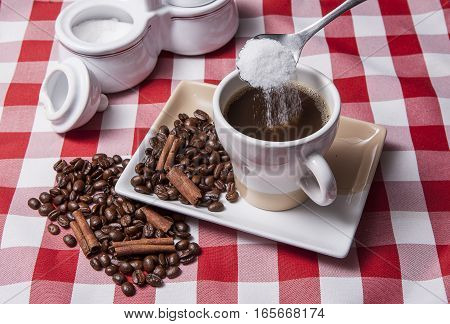 Pouring sugar into cup of coffee by coffee beans and cinnamon.