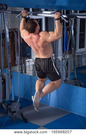 strong, powerful athlete pulls on the bar at the gym