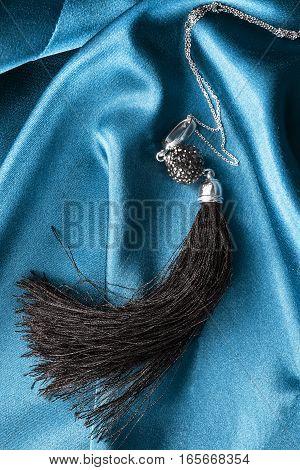 Black tassel pendant on silver chain on blue crumpled satin