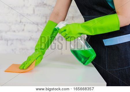 Janitor female hands dressed in protective gloves spraying detergent on the sponge and cleaning table, close-up. Professional cleaning of office