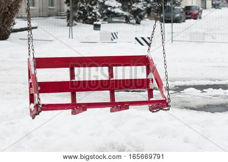 Swing of red pallets on chains over snowy background.