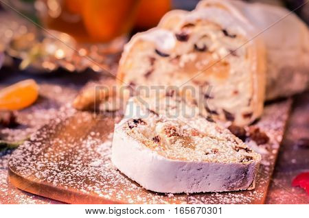 Christmas Cake, Slices of Stollen with Raisins on Rustic Wooden Background with Tangerines. Traditional Festive Dessert. Copy space, Selective Focus, Toned