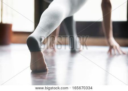 Close up of female stretched barefoot leg in sportswear, grey yoga pants with heel cover for practicing yoga, working out, indoor, home interior background. Back view