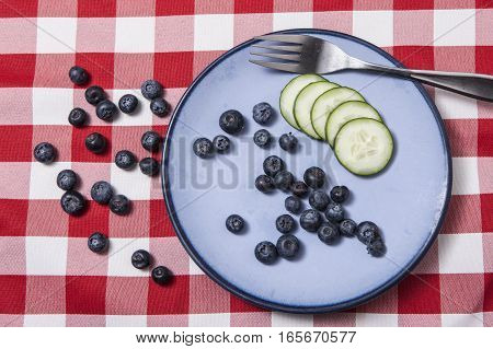 Bluberries and sliced cucumbers on a blue plate.