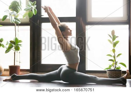 Young attractive woman practicing yoga, sitting in Monkey God, Splits exercise, Hanumanasana pose, working out, wearing sportswear, grey pants, bra, indoor full length, home interior background