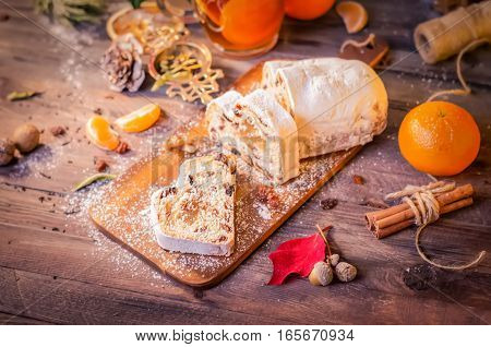 Christmas Cake, Slices of Stollen with Raisins on Rustic Wooden Background with Tangerines. Traditional Festive Dessert. Top View, Copy space, Selective Focus, Toned