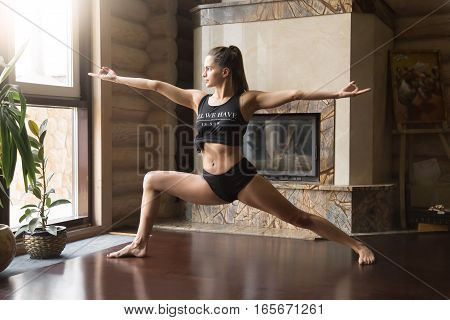 Young attractive woman practicing yoga, standing in Warrior two exercise, Virabhadrasana II pose, working out, wearing sportswear, black tank top, shorts, indoor full length, home interior background