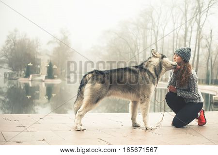 Image of young girl running with her dog, alaskan malamute, outdoor at autumn or winter. Mourning jogging. Healthy lifestyle. Husky. Guide-dog