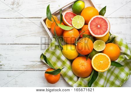 Different citrus fruit in wooden tray on white table. Fruit food background. Healthy eating and diet.
