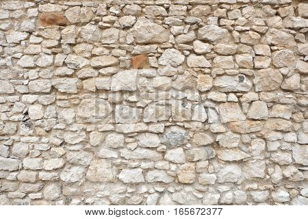 stone wall of and ancient fortress or antique castle, made of white and gray stone blocks in varying irregular sizes and shapes. The facade is an unique abstract texture / pattern.
