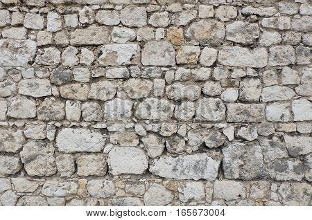 Ancient stone wall of a medieval castle or fortress made of white and gray colored stone blocks with varying shapes and sizes. The irregular structure creates an individual texture.