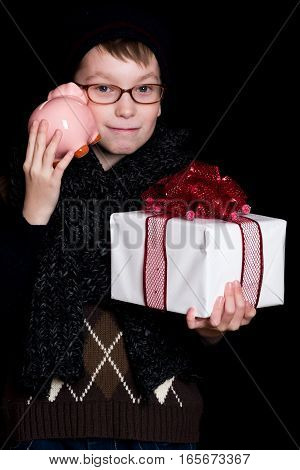small smiling boy or cute nerd kid in glasses hat and fashionable knitted scarf on black background holds white present box with red bow and pink piggy money box
