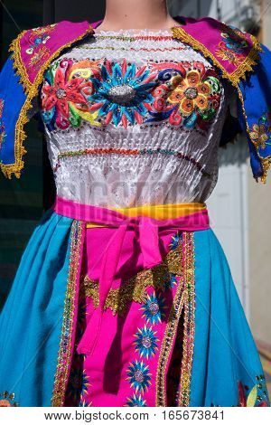 closeup of a colourful emroided Ecuadorian dress in Otavalo