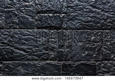 Texture of black stone wall for background.