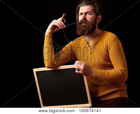 handsome bearded hipster man with long lush beard moustache and stylish hair on thoughtful face in glasses and yellow sweater holding board smoking cigar in studio on black background copy space