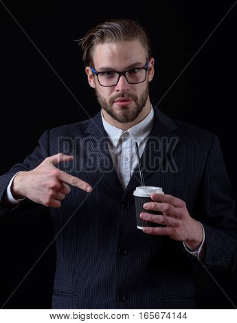 handsome bearded stylish business man in elegant black suit in glasses holding cup of coffee and shows on it in studio on black background