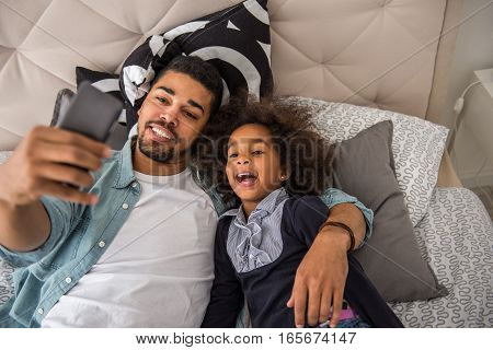 Cute african american girl making selfie with dad.