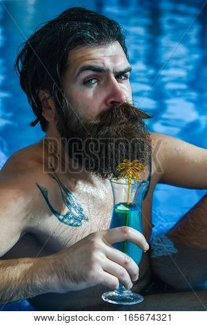 Man Drinks Cocktail In Pool