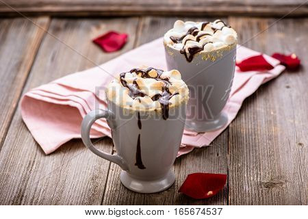 S'mores drink. Two mugs of hot chocolate with marshmallows on a wooden table. Cocoa drink. Rose petals. Valentine.