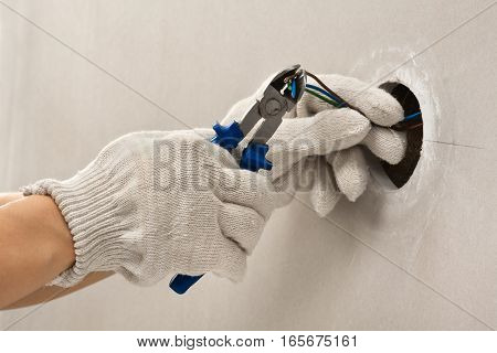 hands of electrician in gloves cutting wires with clippers