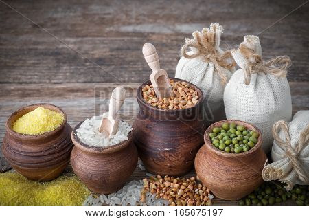 Rustic Clay Pots Filled With Rice, Green Mung, Corn, Buckwheat And Sacks Of Grain On Wooden Table.