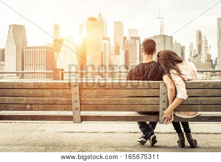 couple relaxing on New york bench in front of the skyline at sunset time. concept about love, relationship, and travel.