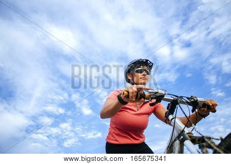 Portrait of cyclist seen from below with blue sky.
