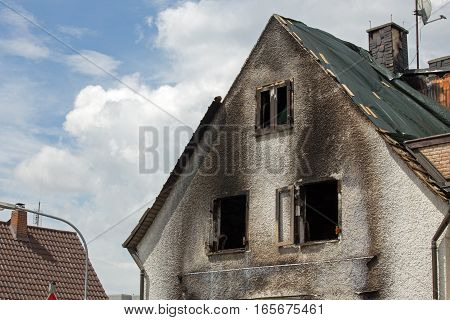 House after a fire, roof covered with tarp