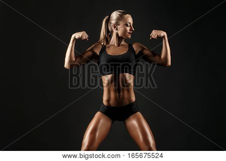 You can say she is a hardworker. Shot of a sporty female blonde girl showing off her perfect body on black background