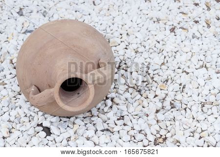 decorative amphora on a ground covered with white stones