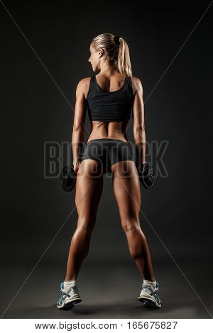 You can say she is a hardworker. Shot of sporty female blonde girl showing back off her perfect body on black background