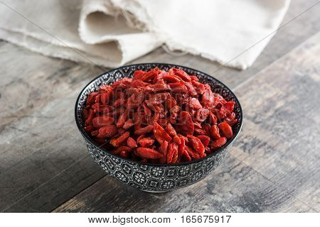 Wolfberries or Goji berries in bowl on wooden background