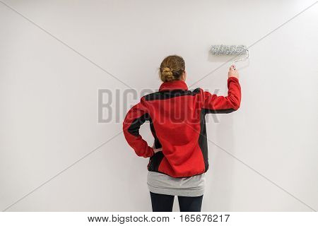 Female Painter With Paint Roller In Front Of Wall As Template