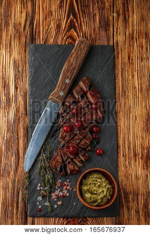 Grilled Sliced Beef Steak With Cranberry, Balsamic Vinegar, Thyme And Spices On A Slate Plate. The P