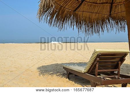 Tropical beach with sun beds and umbrellas protecting from the bright sun.